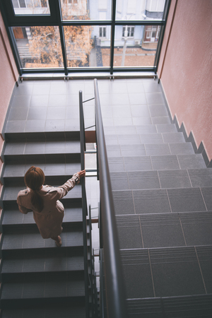 Top view full length lady going steps up in room. Home concept