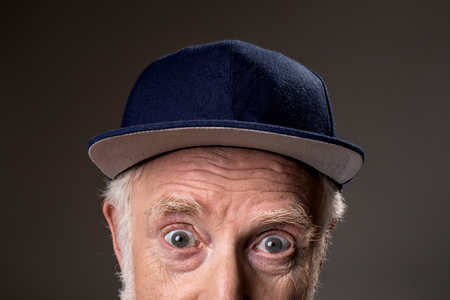 Close up of male half face with jeans cap on top, his eyes open in amazement. Isolated on grey background Stock fotó