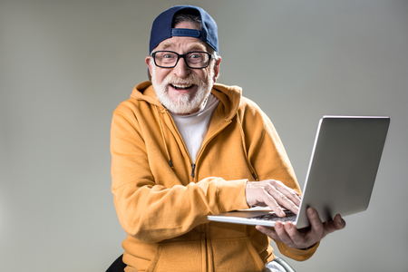 Waist up portrait of trendy pensioner enjoying the use of new laptop. He is looking at camera with big smile. Isolated on grey background