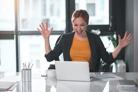 노트북 컴퓨터를 보면서 팔을 흔들며 쾌활 한 사업가의 초상화. 경력과 열정의 개념
