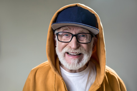 Portrait of bearded old man with hood dressed over the cap. His face expressing positivity. Isolated on grey background