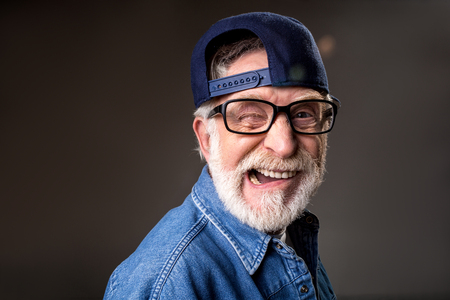 Portrait of jocular old male in cap making funny wry face and winking. Isolated on grey background