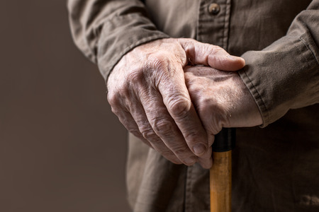 Close up of elderly hands in wrinkles holding walking stick. Isolated on grey background Stock Photo