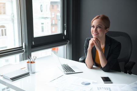 Retrato de la empresaria alegre que tiene trabajo en oficina. Ella sentada a la mesa. Concepto de profesión