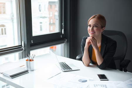 Portrait of cheerful businesswoman having job in office. She sitting at table. Profession concept
