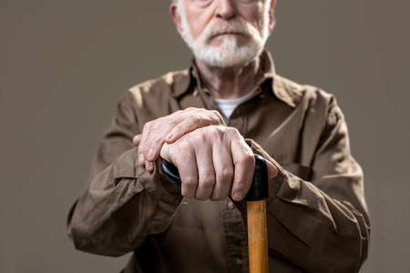 Bearded old man with arms resting on walking cane. Focus on wrinkled hands. Isolated on grey background