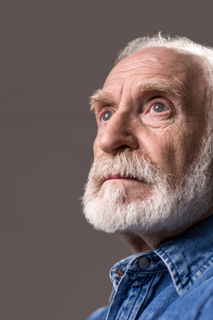 What short life. Low angle of thoughtful old man looking into the distance. Isolated on grey background Фото со стока