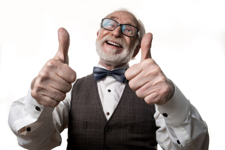 Excellent. Waist up portrait of grayhaired balding senior man holding his thumbs up and smiling. Focus on hands. Isolated on background Imagens