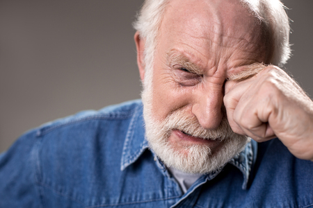 So lonely. Portrait of depressed male pensioner looking at camera and crying. Isolated on grey background