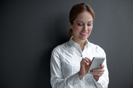 Portrait of beaming young businesswoman typing in phone. Gadget and career concept