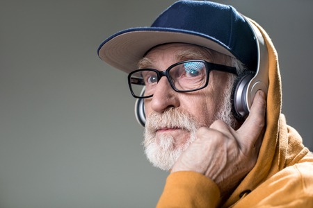 Serious bearded pensioner hearing calm melody in his headphones. Copy space in left side. Isolated on grey background Banco de Imagens - 93329851