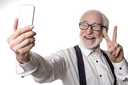 Waist up portrait of jolly oldster making selfie and holding up two fingers. Isolated on background Stock Photo