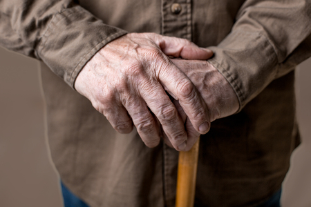 Close up of male wrinkled hands on cane. Isolated on grey background