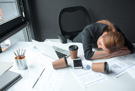 Top view tired businesswoman sleeping on table. Cups of coffee locating on it. Occupation and weariness concept Stock Photo