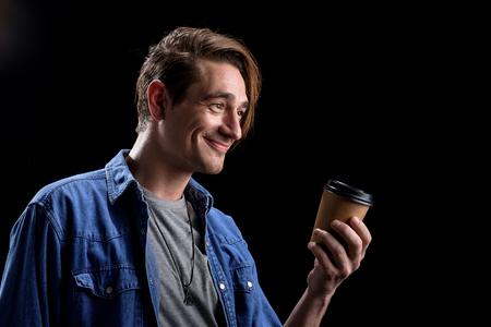 Você gostaria de um pouco de café. O homem novo positivo é estando e guardando o copo do café fresco ao expressar a alegria. Espaço isolado de fundo e cópia no lado direito Foto de archivo - 93517978