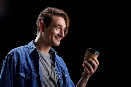Would you like some coffee. Positive young man is standing and holding cup of fresh espresso while expressing gladness. Isolated background and copy space in the right side