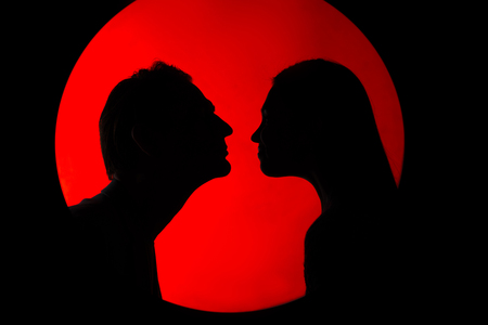 First love. Side view profile of silhouette of amorous couple is standing against super moon. They are looking at each other with affection before kissing. Romantic concept