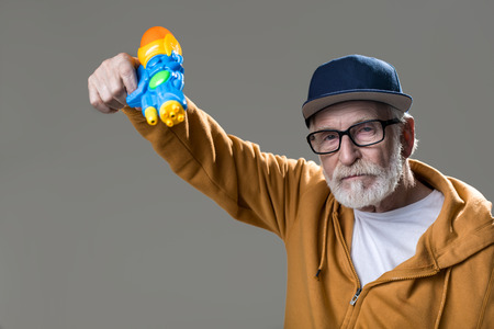 Hands up. Portrait of trendy senior with strong face turning his water gun on camera. Isolated on grey background