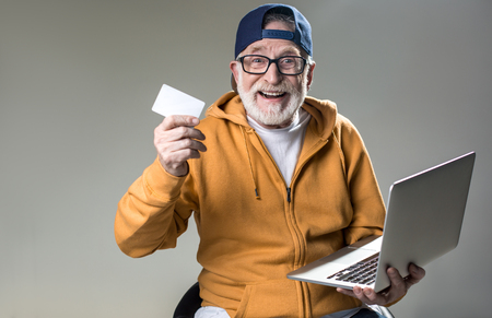 I want to spend pension. Waist up portrait of cheerful old man sitting on chair with notebook and plastic card in his hand. Isolated on grey background