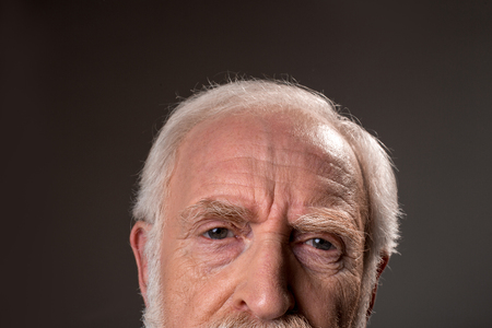 Close up of gray haired male half face wrinkling his forehead, expressing tiredness. Isolated on grey background Stock fotó