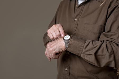 시간은 한순간입니다. 손목 시계를 입고 주름이 손의 닫습니다. 왼쪽에 공간을 복사하십시오. 회색 배경에 절연
