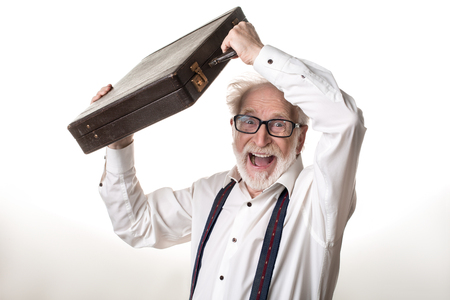 Waist up portrait of delighted old male holding suitcase above his head, expressing excitement. Isolated on background 版權商用圖片