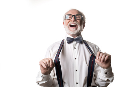 Waist up portrait of joyful old male pulling away his suspenders and laughing. Isolated on background Stock Photo