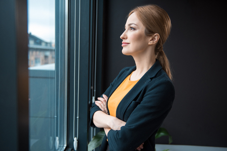 Side view smiling businesswoman watching at window while standing in room. Rest concept