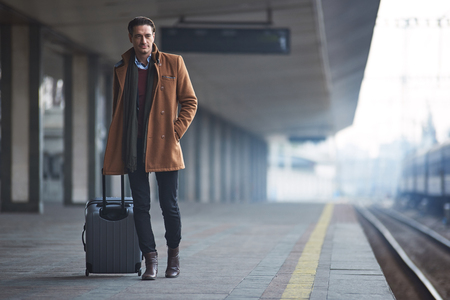 Full length portrait of serene man waiting for train while keeping big baggage. Travel concept. Copy space Stock Photo