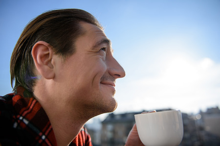 What a good day. Profile of peaceful adult male enjoying his drink outdoor on the balcony. He is having a cup in hands and looking at sky with smile. Copy space