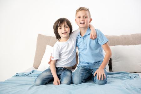 さて、一緒に。ベッドの上に座っている2人の満足した友人がお互いに抱き合う。笑顔でカメラを見ている