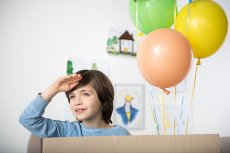 Portrait of smiling boy holding his hand near his forehead and peering into distance joyfully. Air balloons beside him Stock Photo