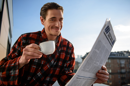 Waist up portrait of happy man looking at camera with satisfied smile. He is having a cup and journal in his hands