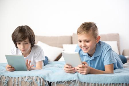 リビングルームで再現する静かな子供たち。タブレットの画面に集中している