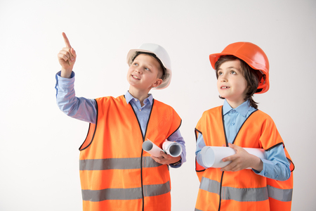 Boys architects with draughts under the armpit discussing the progress of construction with interest. Isolated on background Stock Photo
