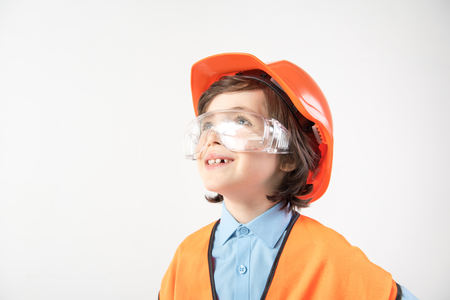 Cheerful child wearing an equipment of his dream job. He is looking aside and laughing. Copy space in left side. Isolated on background