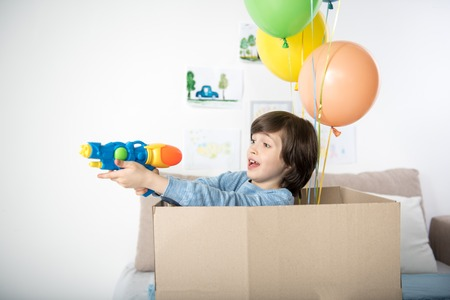 Excited juvenile standing inside of carton and holding toy gun in his hands. Colorful balloons beside him