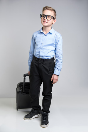 Full length portrait of modish schoolboy getting ready for official journey. He is holding baggage with happiness