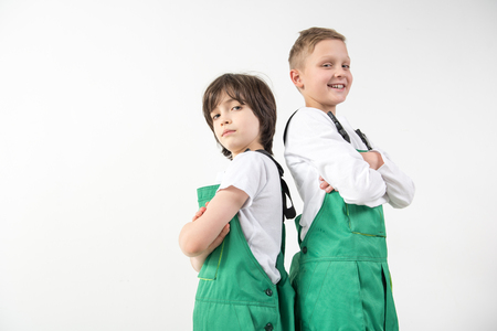 Low angle of young repairmen standing back to back with arms crossed and smiling. Copy space in left side. Isolated on background Stock Photo