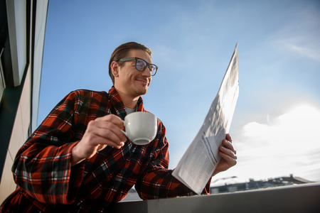 Low angle of satisfied adult male reading daily newspaper with glad smile, holding a cup in his hand. He is standing on the balcony
