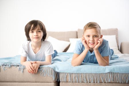 寝具の上で休んでいる2人の少年の肖像画。喜んでカメラを見ている 写真素材