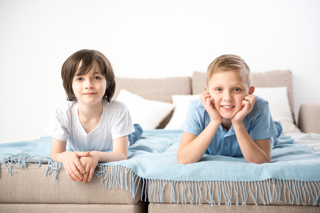 Portrait of two boys resting on bedding. They are looking at camera with pleasure