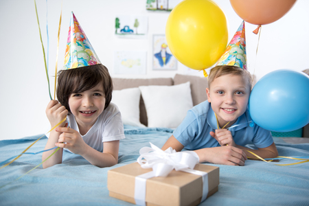 Portrait of two smiling youngsters in colorful cone caps lying on sofa with air balloons in hands, they are looking at camera joyfully. Birthday gift is lying in front of them