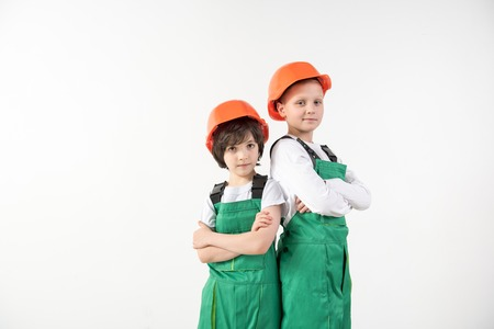 Waist up portrait of two like minded male person wearing builder clothing. They are looking at camera with gravity. Copy space in left side. Isolated on background Stock Photo