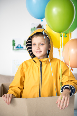 Waist up portrait of smiling boy wearing yellow raincoat, he is standing inside of cardboard box. Beautiful balloons above him