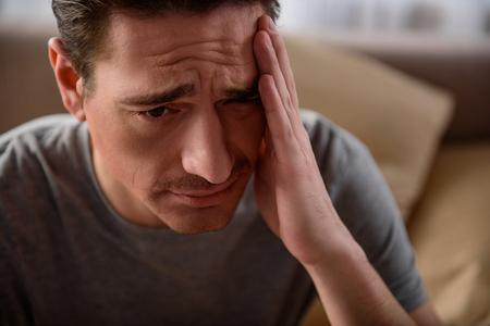 痛いの頭痛に苦しむ疲れた男の肖像画をクローズアップ。彼は動揺して寝室に座っている。彼の顔に焦点を当てる 写真素材