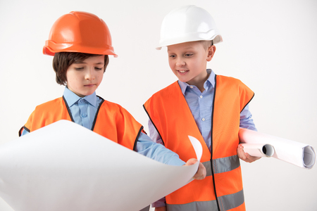 Two concentrated boys in helmets looking at drawing with interest. Isolated on background