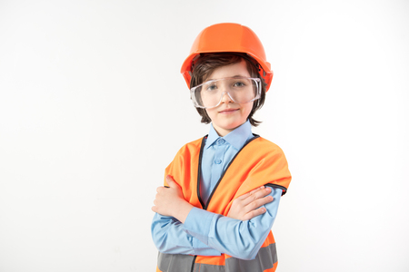 Portrait of serious child with crossed arms planning his career of an architect. He is looking at camera. Isolated on background
