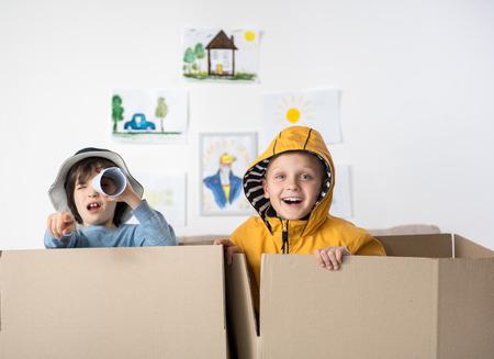 Regardez là. Portrait de mignons jeunes heureux faisant semblant de naviguer en bateau, l'un d'eux regarde à travers un morceau de papier roulé et en montrant la caméra