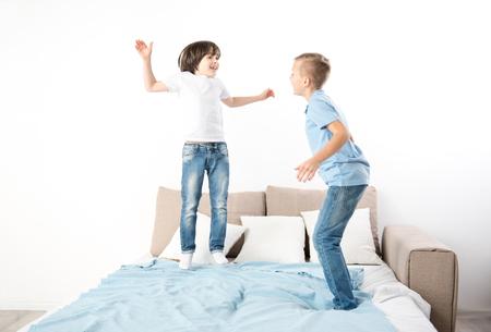 リビングルームで楽しい時間を過ごしている小さな兄弟。ベッドに飛び乗る 写真素材